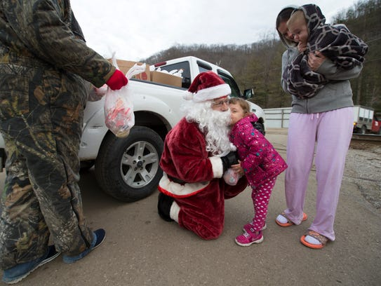 Mike Howard, left, the Mountain Santa, hugged a young
