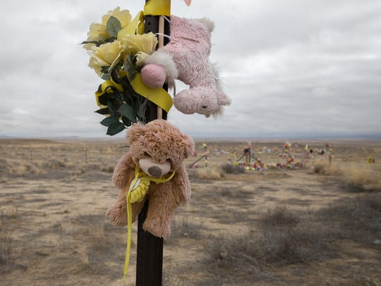 A teddy bear hangs on a sign post on Tuesday near a