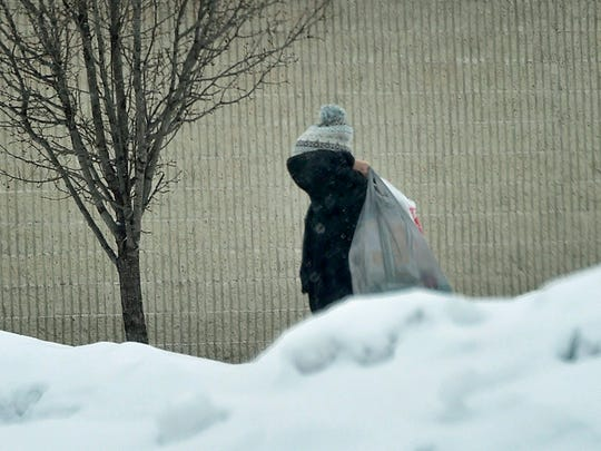 A pedestrian walks past huge plowed snow banks Monday, Feb. 15, 2016 at Southgate Shopping Center.  Light snow and freezing rain fell for much of the day.