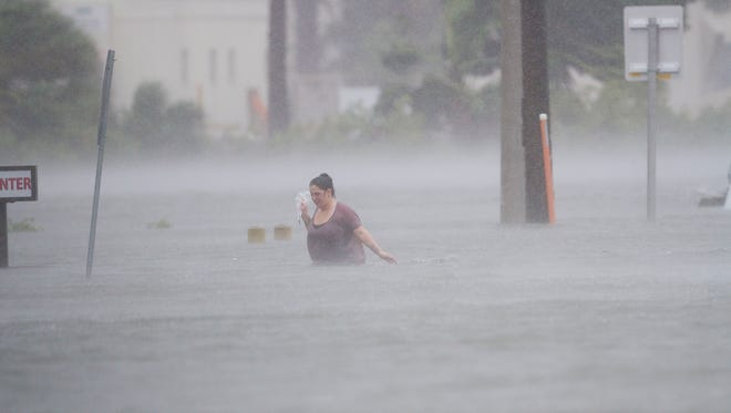 An unidentified woman makes her way through a flooded street in St. Augustine on Friday.  Hurricane Matthew is skirted the area causing major flooding, especially in downtown St. Augustine.