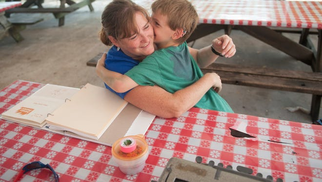 Henry Norton, 6 of Mount Laurel,  who was born deaf and is now nearly blind from a rare genetic disease called Usher syndrome hugs deafblind intervener Lauri Wendel after succesfully practicing using a braille writer to spell words at Liberty Lake Day Camp in Bordentown.  08.13.14
