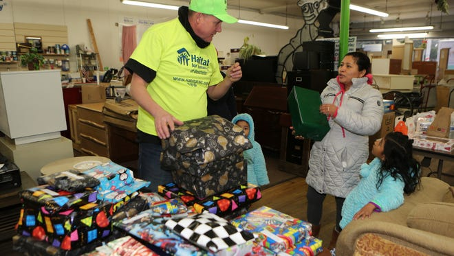 Jim Killoran, the CEO of Habitat for Humanity of Westchester, hands out gifts to Regina Hernandez during the Three Kings Day celebration and breakfast at the Re-Store on Main Street in New Rochelle, Jan. 7, 2017.