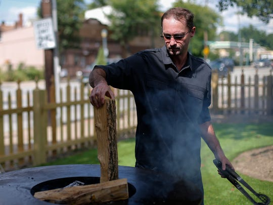 Denver Cavins loads the Artflame grills with wood, Thursday, Sept. 1, 2016, at Casa Figueroa in Pleasant Ridge.