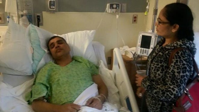 Khada Katel lies in a hospital bed as his wife looks over him.