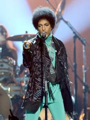 Prince performs onstage during the 2013 Billboard Music