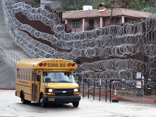 In this Monday, Feb. 4, 2019 photo, a school bus rolls past the concertina wire-covered fence at East International and Nelson Streets in downtown Nogales, Ariz.