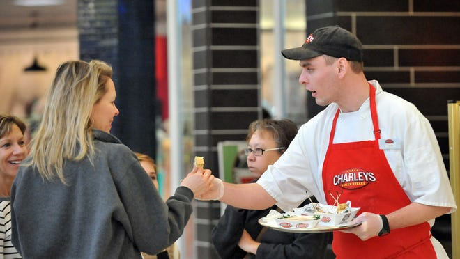 Ryan Simmons hands out chicken teriyaki sandwich samples in front of Charleys Philly Steaks in the River Valley Mall food court.