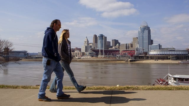 People cast a shadow at they walk along Newport River walk with Cincinnati Skyline and Great American Ball Park in the background Saturday March 22, 2014 in Newport.