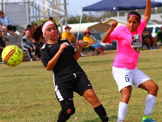 Alamogordo's Kayla Duran, right, sends a ball past a Santa Teresa defender Saturday afternoon.