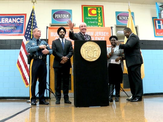 New Jersey Governor Phil Murphy speaks before signing an Executive Order on gun safety at the Dr. Martin Luther King Middle School in Asbury Park Friday, April 6, 2018.   Also shown at left is State Police Colonel Patrick Callahan and Attoney General Gurbir Grewal, and at right is middle school 8th grader Jaione Murray, 14, and Dr. Lamont Repollet, Acting Commissioner of the State Department of Education.