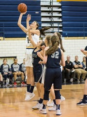 Dakota High School's Rachel Baur (4) reaches to block a shot by Port Huron Northern's Sarah Wight during their basketball game at Port Huron Northern High School Feb. 1.