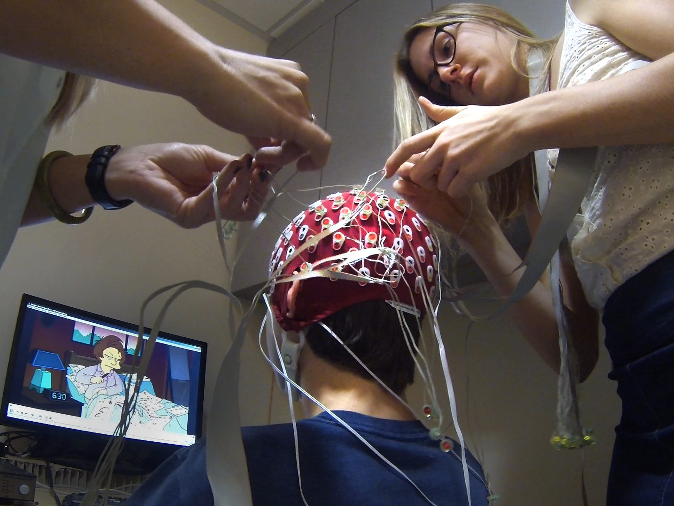 "Zack Monterosso watches an episode of ""The Simpsons"" as EEG technicians Mallorie Lenn, left, and Chantelle Kinzel monitor him. Monterosso is part of a study to understand the risk factors for the development of psychotic behavior at the Institute Semel Institute for Neuroscience and Human Behavior at UCLA."