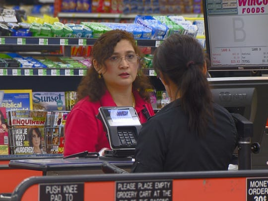 A Winco checker rings up a customer.