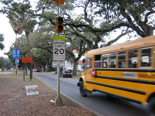 A school bus rolls past a school zone sign.