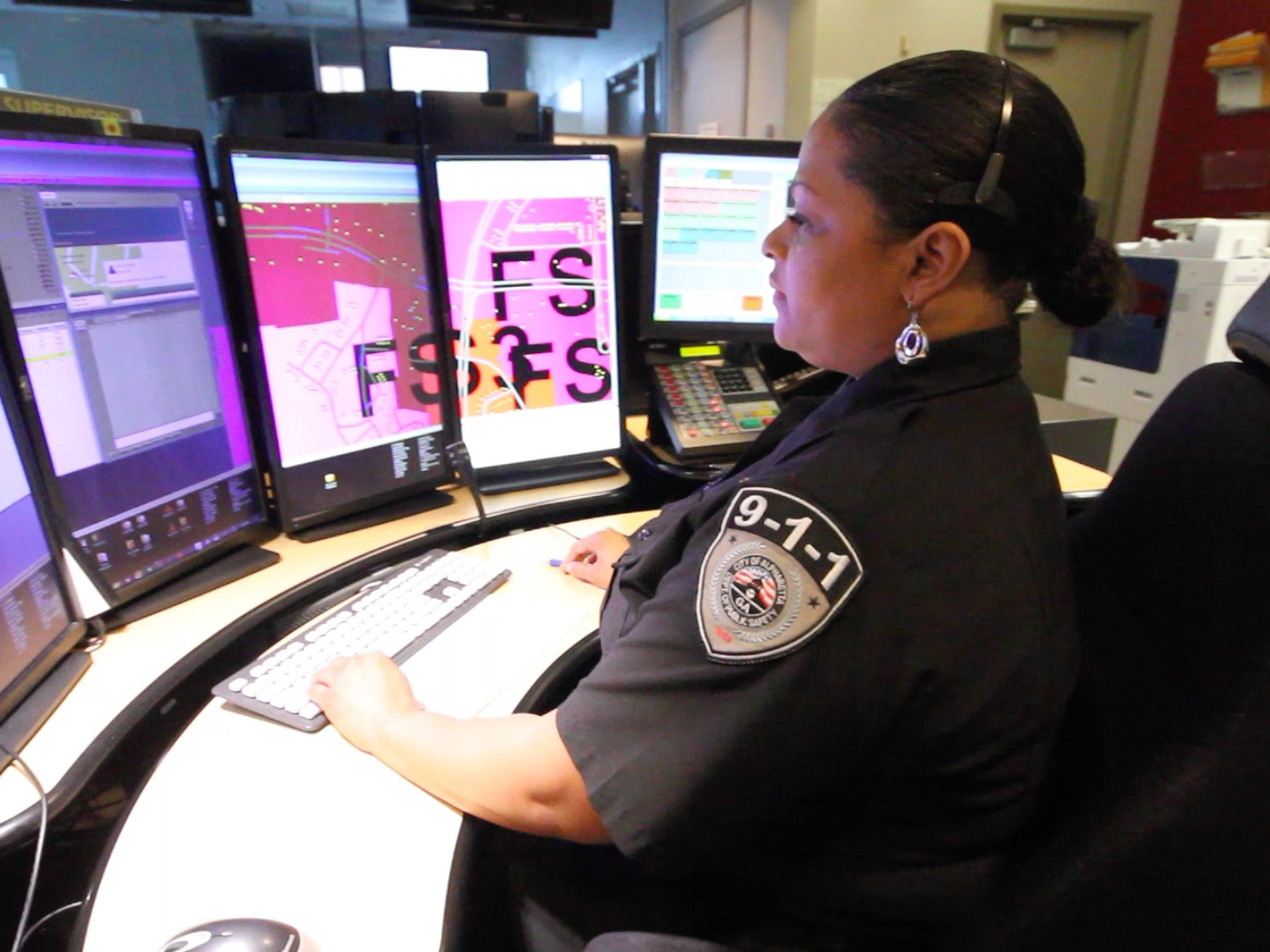 A dispatcher surveys her bank of monitors at the 911