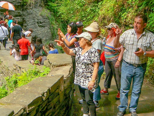 Visitors to Watkins Glen State Park walk near the bottom