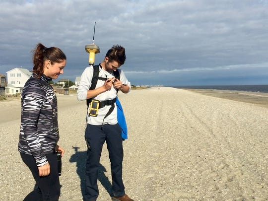 University of Delaware College of Earth, Ocean and Environment students Stephanie Dohner and Time Pilegard use equipment to measure Broadkill Beach on Wednesday. Weekend storms eroded the shoreline.