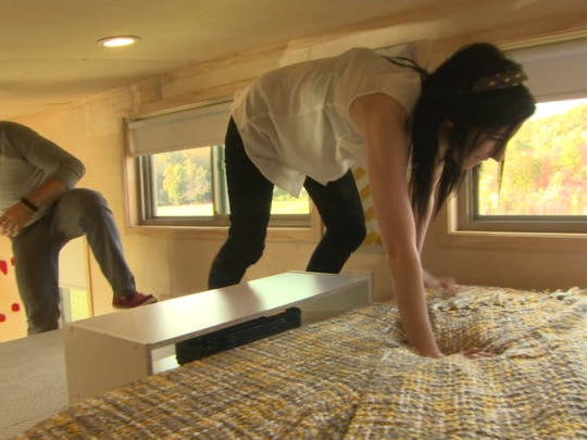 Vincent Sorgentoni and Sam Adams climb into the loft in their tiny house.