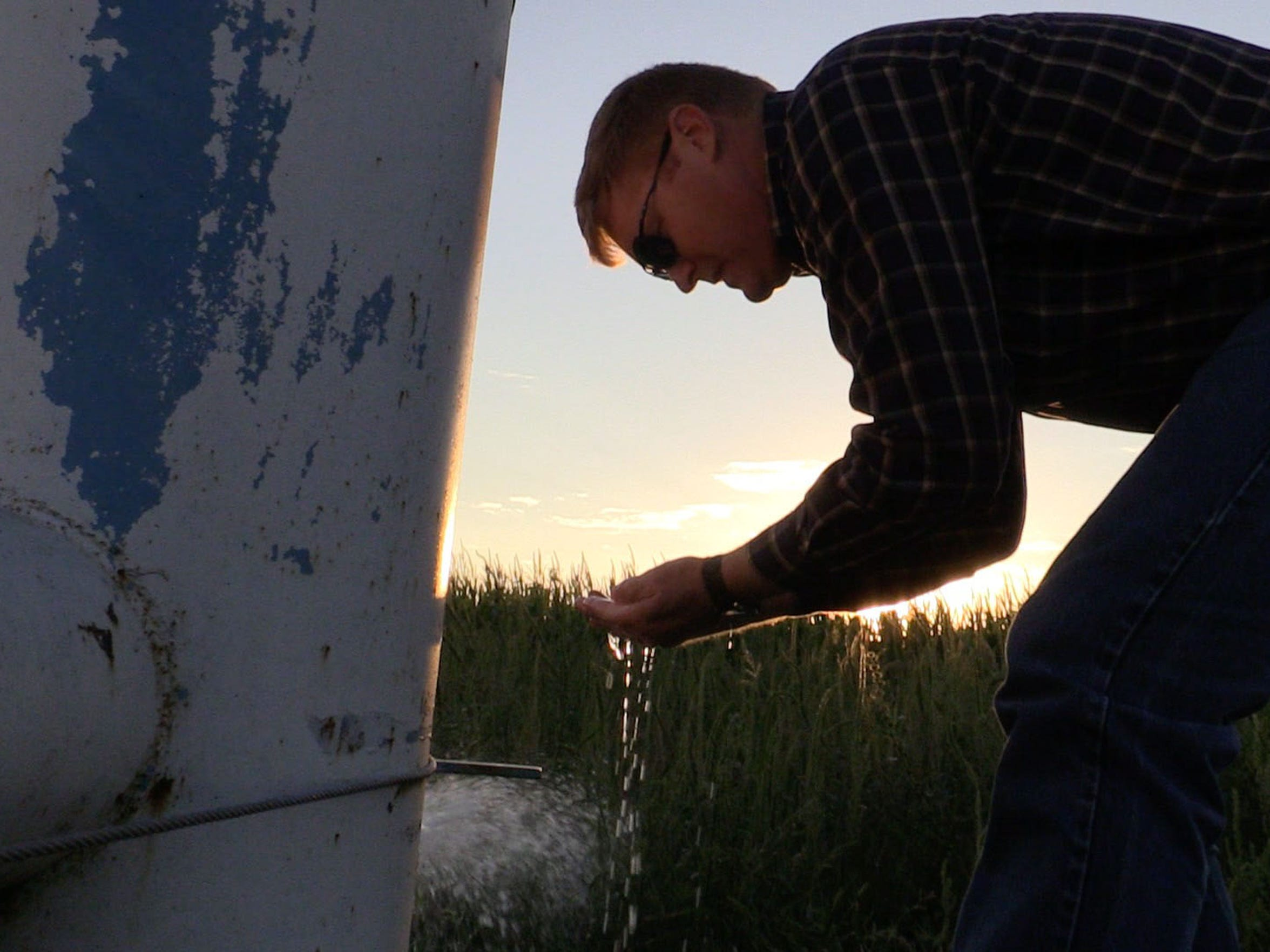 Jay Garetson lets water run into his hands from a well on his family's farm near Sublette, Kansas. He saw fine bubbles in the water and said that indicates the well is weakening as the Ogallala Aquifer declines. He said he's worried about the future of farming in the area.