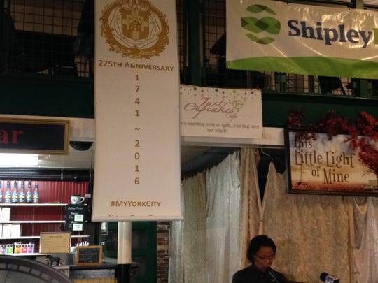 A banner commemorating York's 275th anniversary hangs behind York Mayor Kim Bracey as she speaks to a small crowd at Central Market on Thursday.