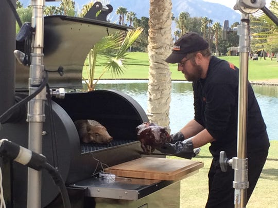 "Chef Chris Lynch pulls out a suckling pig from a smoker during a scene of ""Project Smoke""  being filmed at the Doubletree Resort in Cathedral City, February 2, 2016."