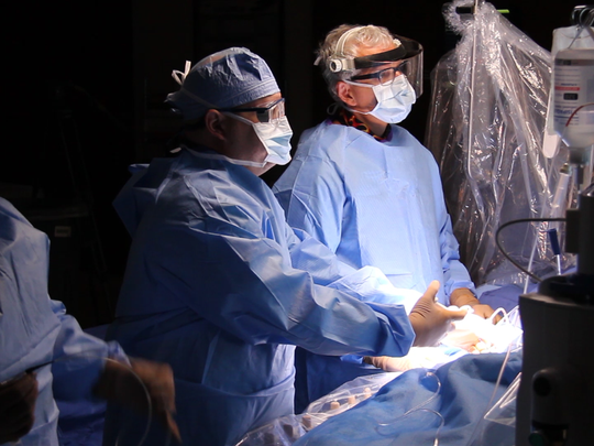 Dr. Dixon, middle, works with his fellow doctors in the cath lab to remove a clot from a patient.