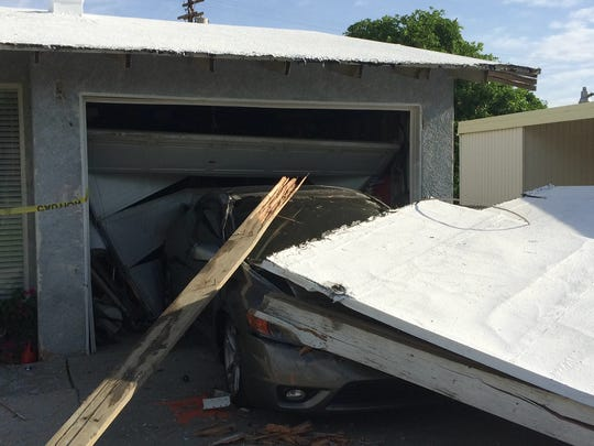 A damaged carport and Honda Civic sit outside an Indio home that was struck several times by a pickup Sunday evening. Several people suffered major injuries and a suspect was arrested.