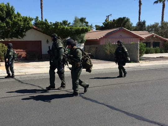 SWAT Team members walk on Avenida Quintana following a standoff in Cathedral City Thursday. One man was arrested and two others were detained.