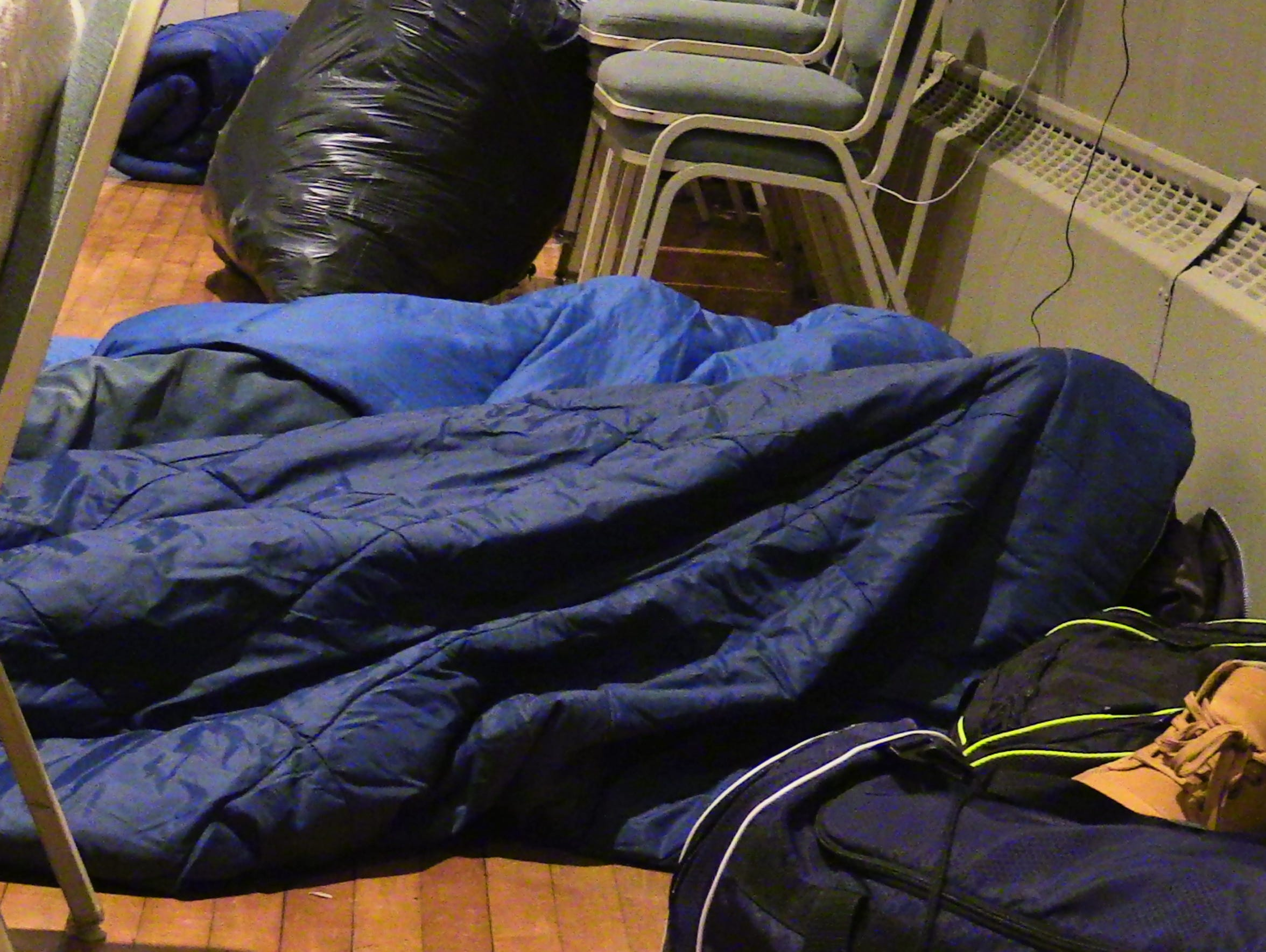 Homeless men settle in for the night March 30 at the