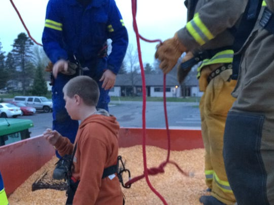 Firefighters remove corn from a large bin Monday, April 26, 2016, at the Pittsville Fire Department, to bury Alexander Kumm, 12, in it up to his waist. The firefighters then rescued Alexander from the bin.