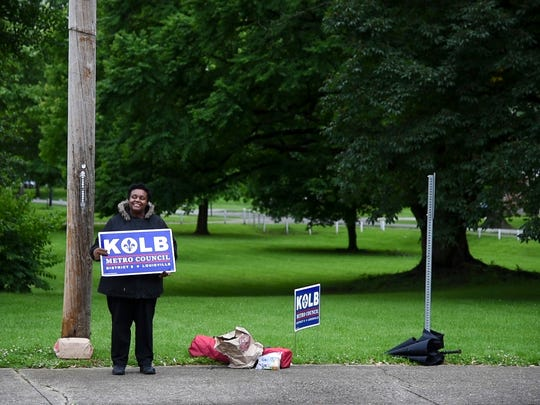 Latonya Bright waved at passerby as they pulled into Atherton High School in Louisville, KY to vote on Tuesday's election. Bright held the sign high in hopes voters would pick Chris Kolb for District 8 Metro Council.
