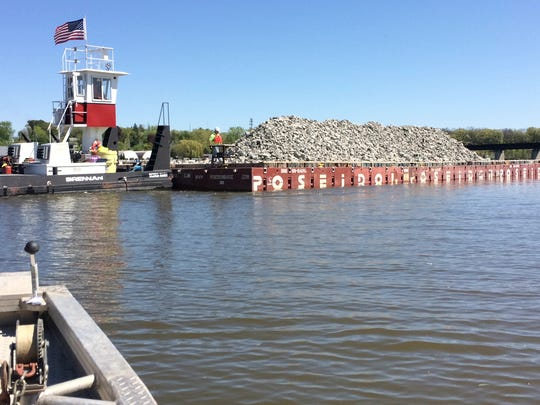 Some areas of the river will be capped to bury PCBs, rather than dredged. The Poseidon hauls a load of rock to an area near the Interstate 172 bridge to be capped.