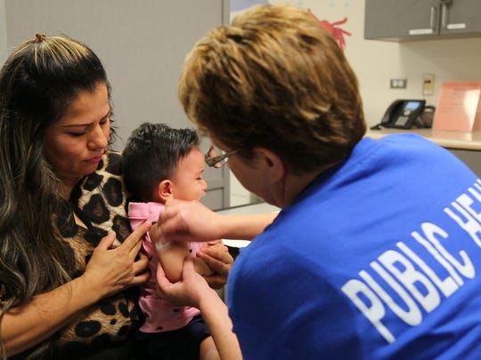 Marcia Rodriguez holds her child as nurse Diane Dickinson
