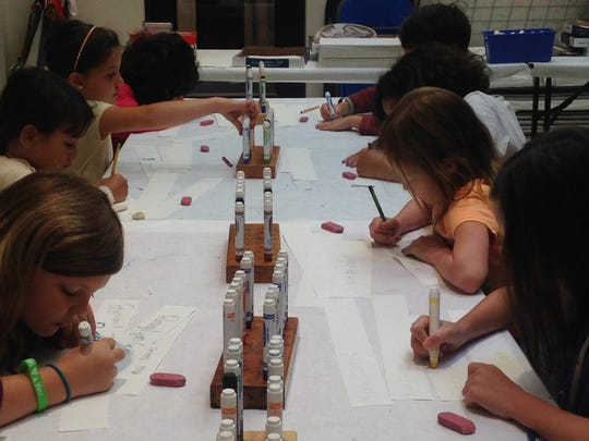 Children color their portfolio name tags during the  first week of Summer Art Camp held at the Montgomery Museum of Fine Arts.