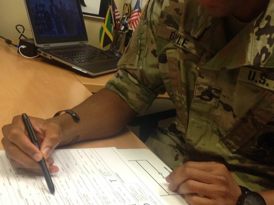 Sgt. 1st Class Sheldon Gayle goes over preliminary information for a recruit looking to become a soldier.