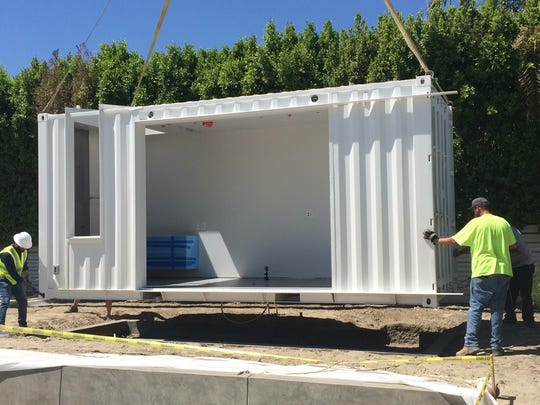 A shipping container that will become a pool cabana gets dropped off in the backyard of a 1960 Alexander home in Palm Springs owned by John Winter.
