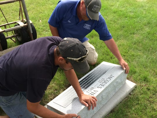 Workers install the stone for Jacques Vieau at the