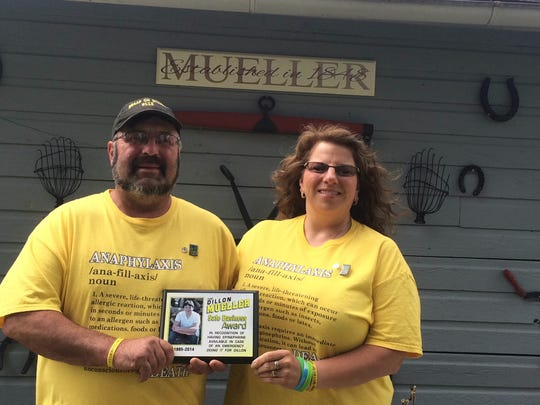 George and Angel Mueller stand outside their home with a Dillon Mueller Safe Business Award.