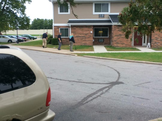 Detectives search the grass Friday morning following a Thursday night shooting outside an apartment building in the 800 block of Lime Kiln Road.