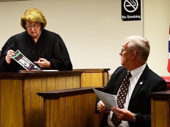 Gibsonburg police Chief Paul Whitaker tells visiting Judge Patricia Cosgrove about photos taken of his home.