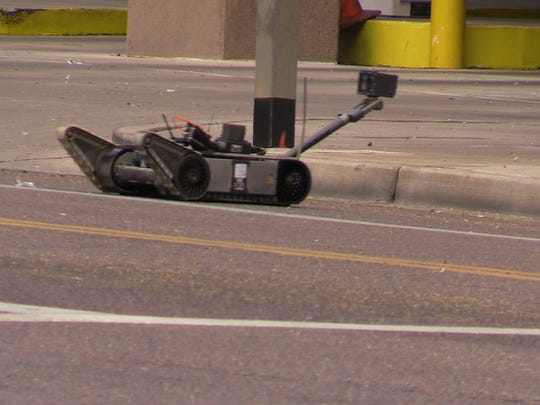 A bomb disposal robot leaves the scene of a parking