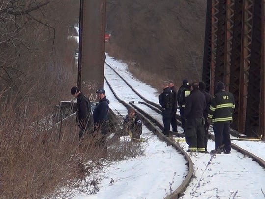 Emergency responders stand on the Burlington side of the Blue Bridge at the Intervale and look down below during the beginnings of a body recovery process on Sunday, Jan. 1, 2017. Police say a man's body was lying on land below the bridge.