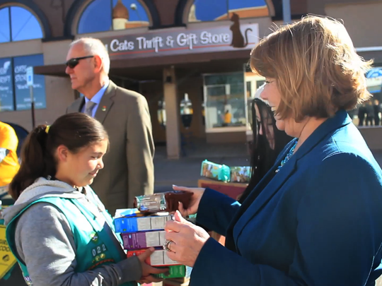 Kim Boss bought some Girl Scout cookies while on set of the Alamogordo Mannequin Challenge. Mayor Richard Boss looks  on in the background in Alamogordo's Historic Downtown Sunday, Feb. 19.