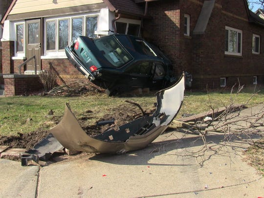 A car crashed into a Battle Creek house Monday and the bumper from another car was in the yard; a witness said he saw two cars racing down Harvard Street.