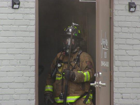 A Battle Creek firefighter stands at the back door