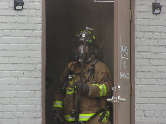 A Battle Creek firefighter stands at the back door of LynnIvan Salon in downtown Battle Creek Monday. A utility pole caught fire and collapsed onto the roof of the building.