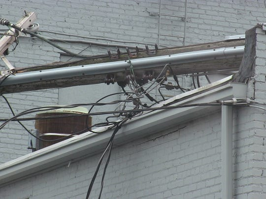 A collapsed utility pole sits on the roof of LynnIvan Salon in downtown Battle Creek Monday.