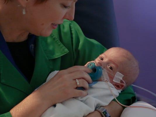 Preemie cuddled by volunteer