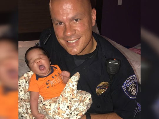 Officer Tommy Norman holds baby Xavier.