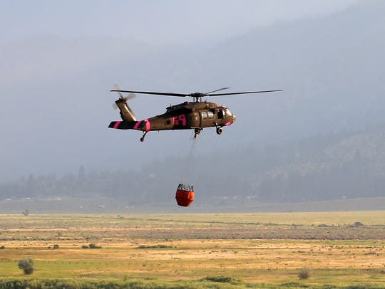 Helicopter carrying water drop to Brenda fire in Washoe
